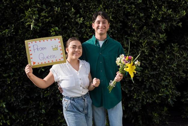 Couple souriant de plan moyen avec des fleurs