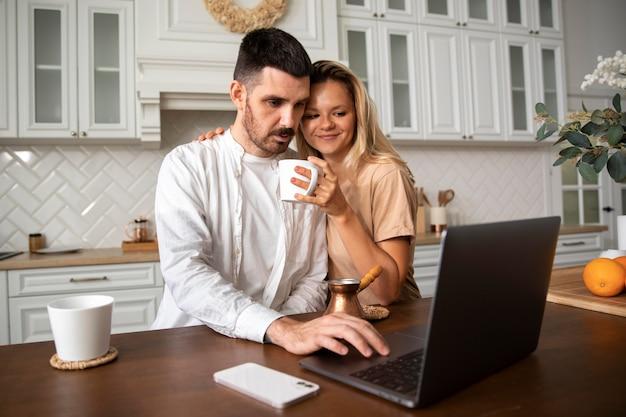 Couple souriant à plan moyen avec ordinateur portable