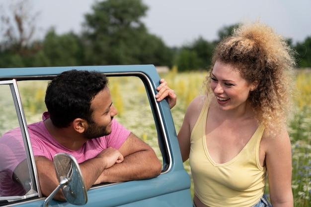 Couple souriant à plan moyen avec van
