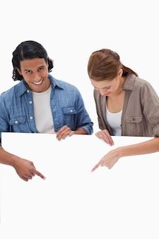 Couple souriant pointant vers le bas sur un mur blanc
