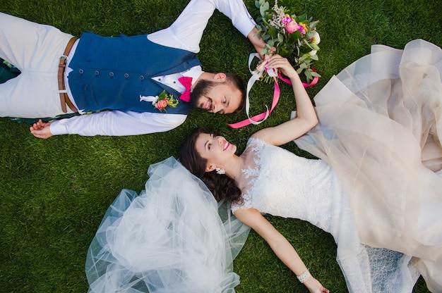Couple souriant portant sur l'herbe