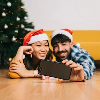 Couple souriant prenant selfie à noël
