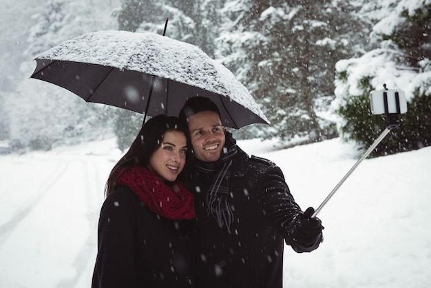 Couple souriant prenant selfie sur téléphone mobile pendant les chutes de neige