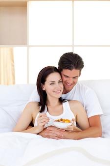 Couple souriant prenant son petit déjeuner