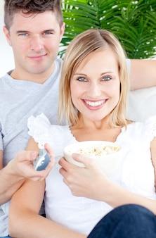Couple souriant en regardant la caméra avec un cadeau