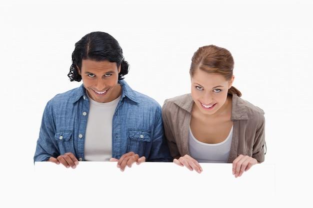 Couple souriant, regardant par-dessus le mur blanc