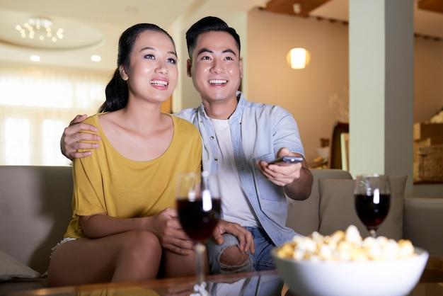 Couple souriant, regarder la télévision sur le canapé