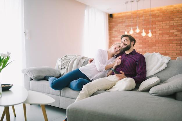 Couple souriant, regarder la télévision à la maison