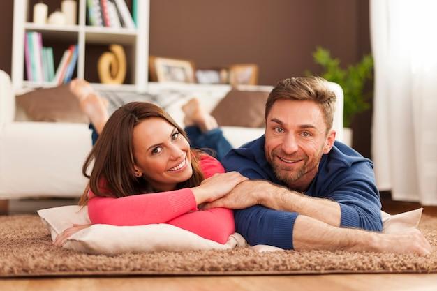 Couple souriant reposant sur un tapis à la maison