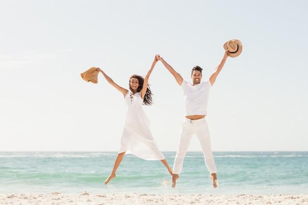 Couple souriant sautant ensemble