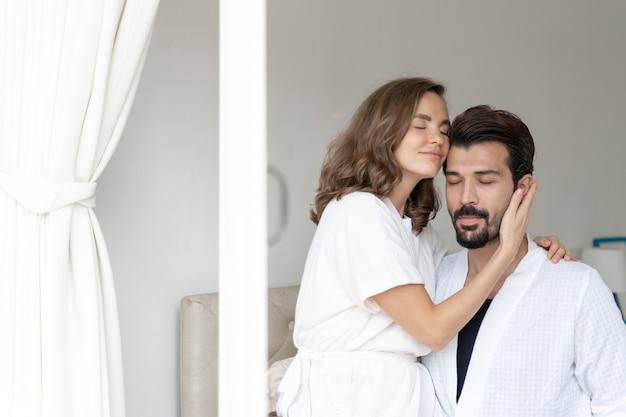 Couple souriant se détendre et couples câlins au lit