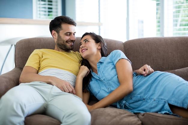 Couple souriant se détendre dans le salon à la maison