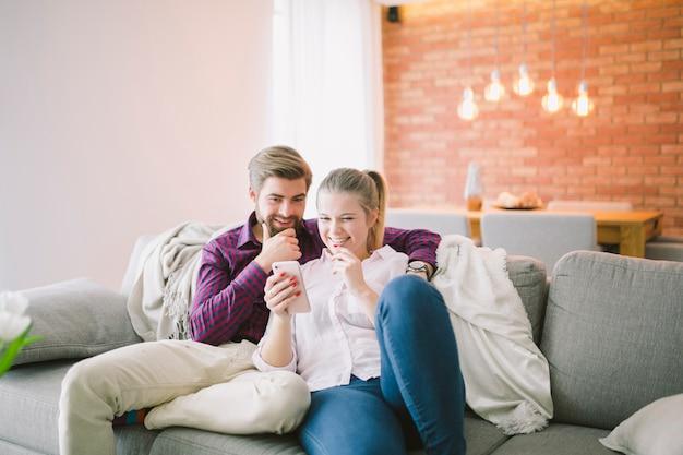 Couple souriant avec smartphone