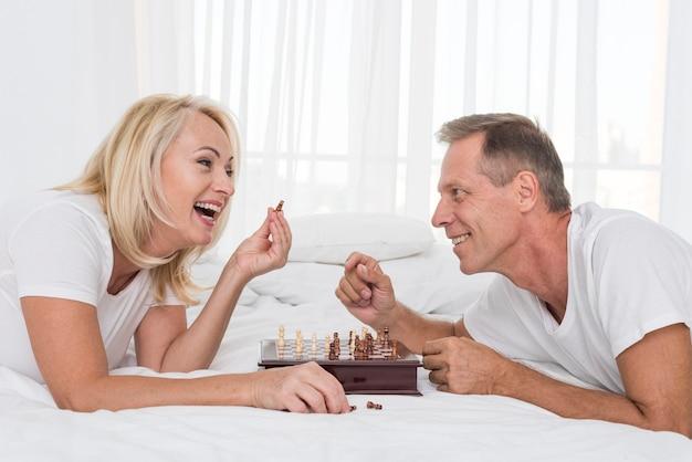 Couple souriant smileys jouant aux échecs dans la chambre