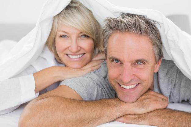 Couple souriant sous les couvertures