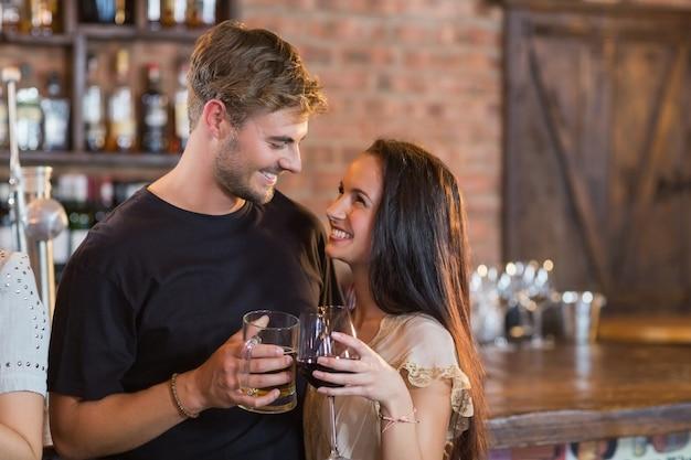 Couple souriant tenant des boissons