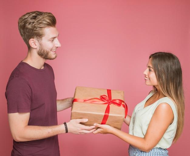 Couple souriant tenant la boîte cadeau sur fond coloré