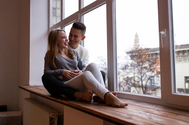 Couple souriant tout en étant assis près de la fenêtre à la maison