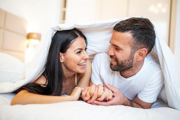 Couple souriant va s'embrasser sous des draps de couchage le matin.