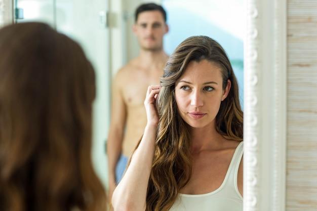 Couple, sourire, devant, miroir salle bains, chez soi