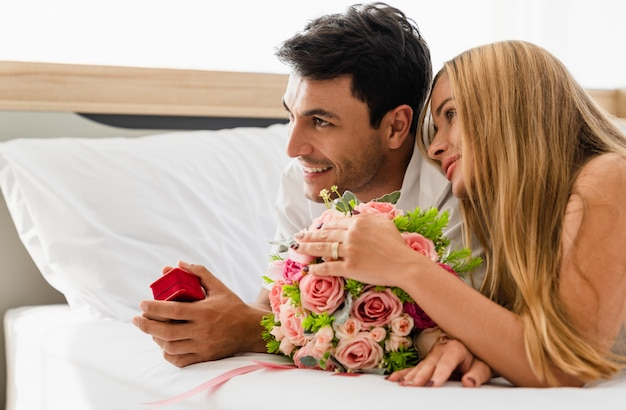 Couple, sourire, heureux, amant, lit, tenue, épouser, anneau, boîte, mains