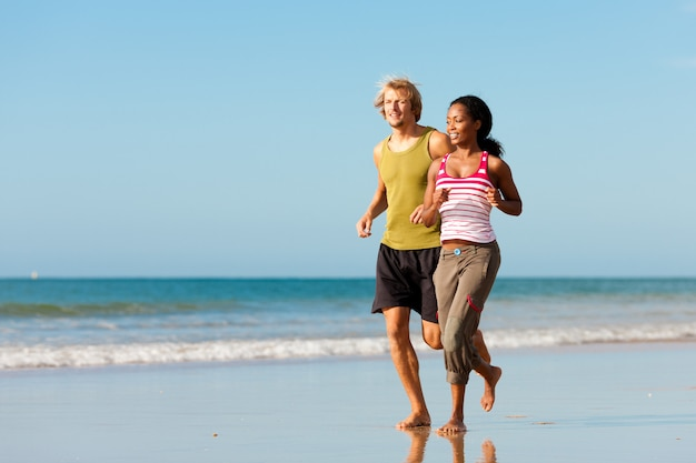 Couple de sport jogging sur la plage