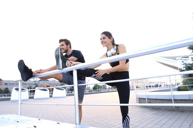 Couple sportif de coureurs étirant les muscles de la jambe, s'échauffant avant de courir à l'extérieur pour l'entraînement des athlètes.