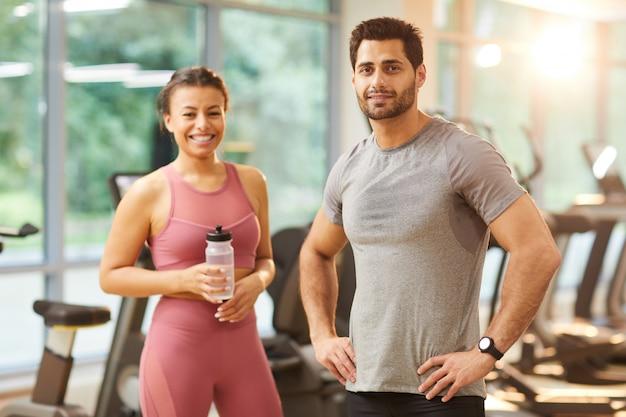 Couple sportif posant dans une salle de sport
