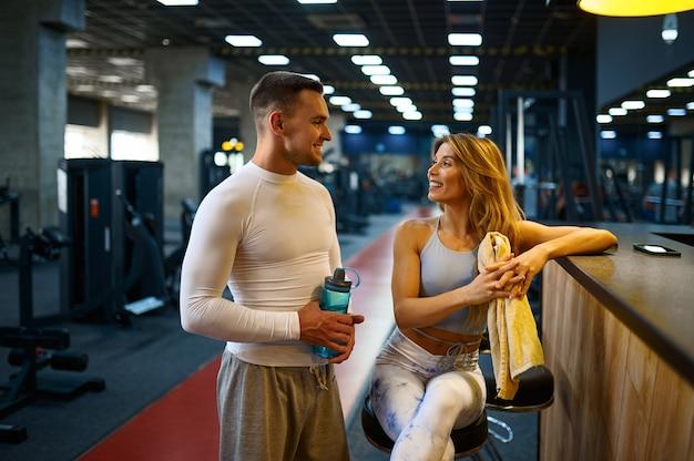 Un couple sportif se détend au comptoir du bar de la salle de sport après l'entraînement physique