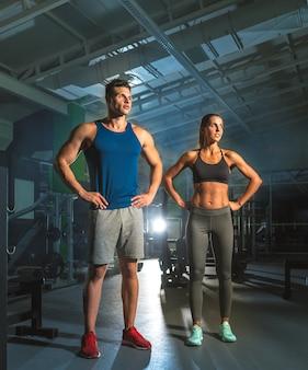 Le couple sportif se tient dans la salle de gym sur le fond clair