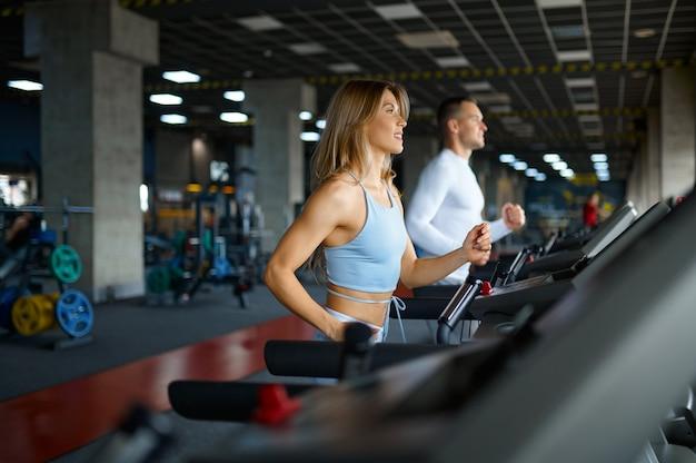 Couple sportif sur tapis roulant, entraînement en salle de sport