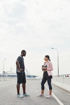 Un couple de sportifs africains se parle lors de leur réunion à l'extérieur, ils discutent de sport ex...