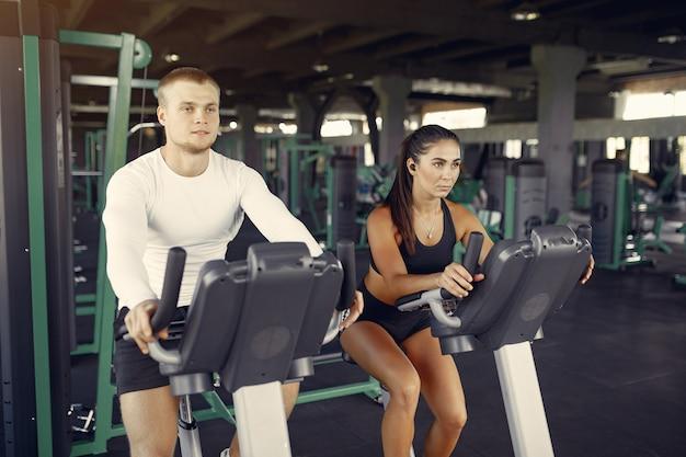 Couple de sportifs dans une formation de vêtements de sport dans une salle de sport