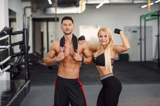 Couple de sportifs posent dans la salle de gym après une séance d'entraînement. un jeune homme a serré sa petite amie dans la taille.