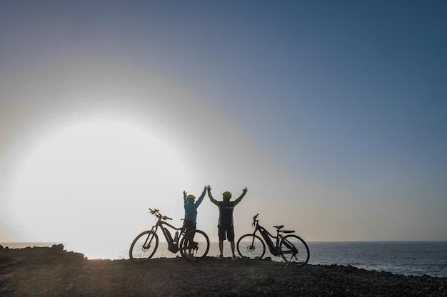 Couple de sportifs seniors aux bras levés profitant de la liberté et d'une activité saine. concept de vacances et de sport. lumière du coucher du soleil