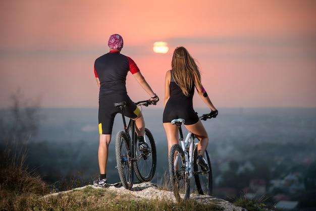 Couple, sports, vélos, debout, sommet, colline, apprécier, coucher soleil