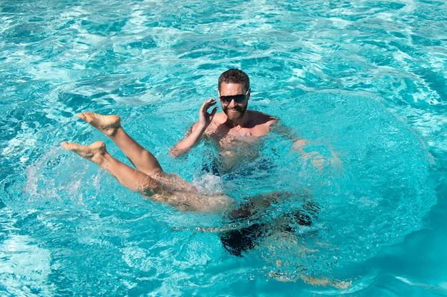 Couple de station balnéaire d'été dans la piscine loisirs d'été actifs