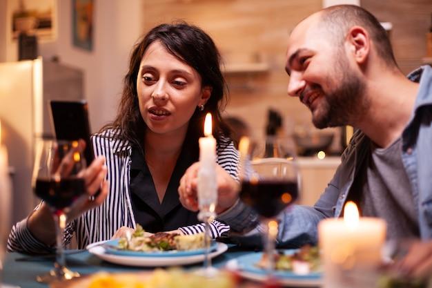 Couple surfant sur internet à l'aide d'un smartphone pendant un dîner romantique dans la cuisine. des adultes assis à table dans la cuisine naviguant, cherchant, utilisant des smartphones, internet, célébrant un anniversaire.