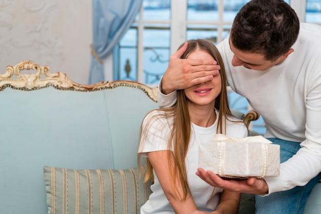 Couple surprenant avec cadeau sur canapé