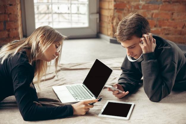 Couple surpris et étonné attrayant à l'aide d'appareils ensemble