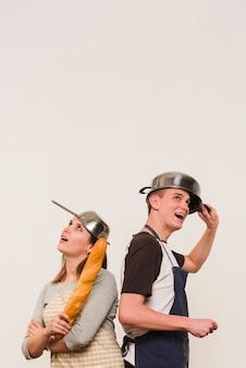 Couple en tablier debout avec batterie de cuisine sur la tête