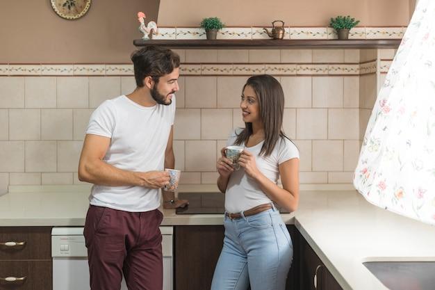 Couple avec des tasses dans la cuisine le matin