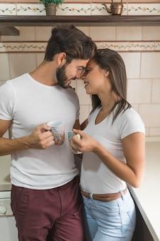 Couple avec des tasses touchant le nez