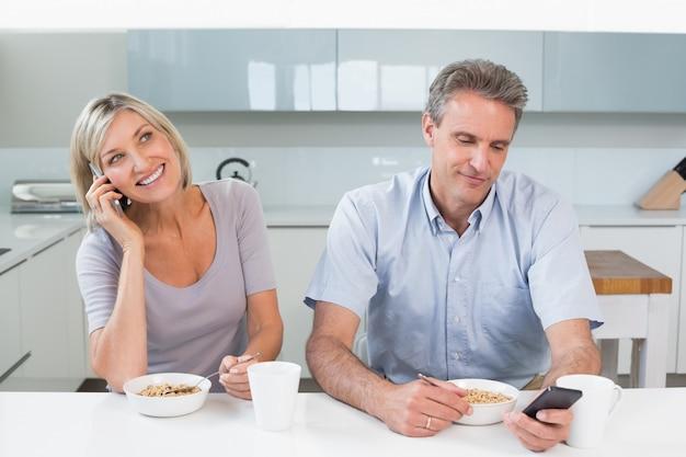 Couple avec un téléphone portable en prenant son petit déjeuner