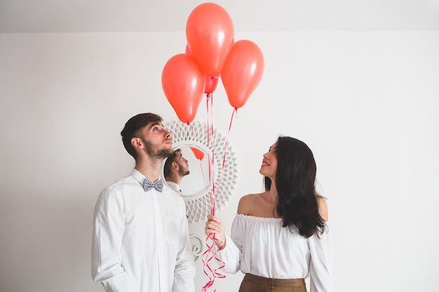 Couple tenant des ballons avec forme de coeur