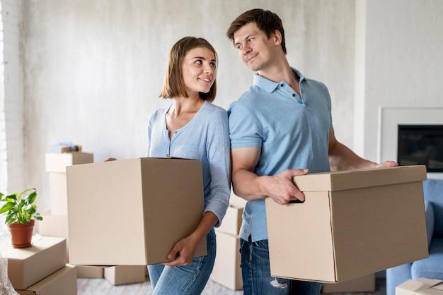 Couple tenant des boîtes pour le jour du déménagement
