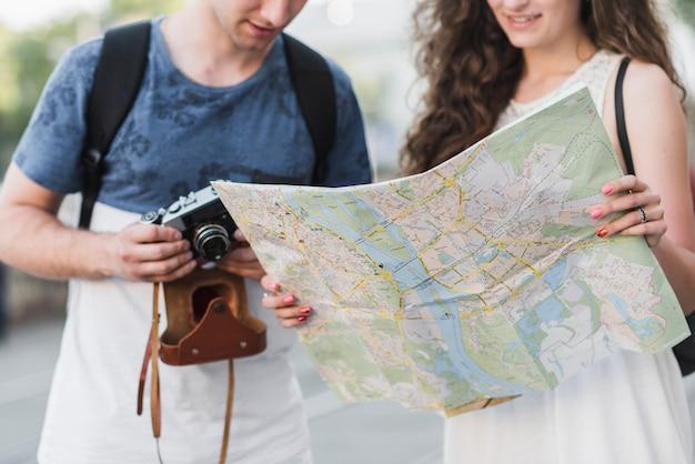Couple tenant la carte et le vieil appareil photo