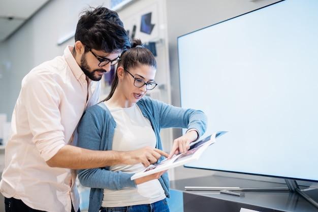 Couple tenant le catalogue et pointant sur la télévision intelligente qu'ils aiment. concept de nouvelles technologies.