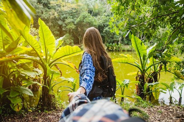 Couple tenant la main et aller vers une forêt