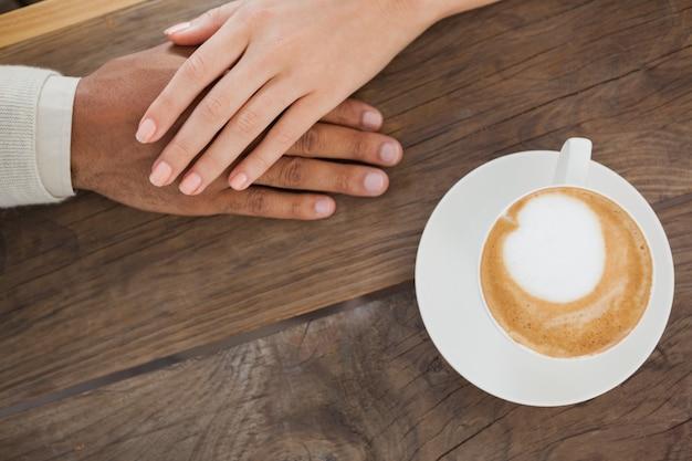Couple, tenant mains, à côté de cappuccino